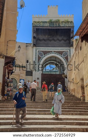 Fes, Morocco - May 11, 2013: Locals and tourists walking in the medina in Fes, on the steps leading to an ornate gate decorated with mosaic - stock photo