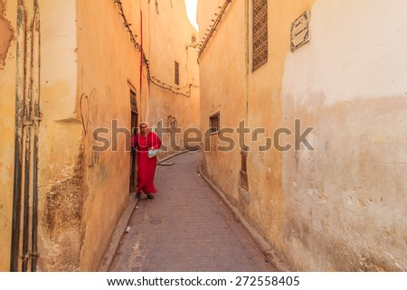 Fes, Morocco - May 11, 2013: Woman wearing a kaftan, traditional Moroccan clothing, stepping out into a narrow street in Fes Medina in Morocco - stock photo