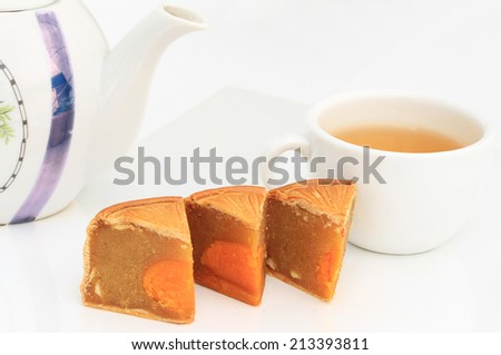 Festival Moon cake with nuts and yolk inside and hot tea in white cup - chinese dessert sweet food. - stock photo