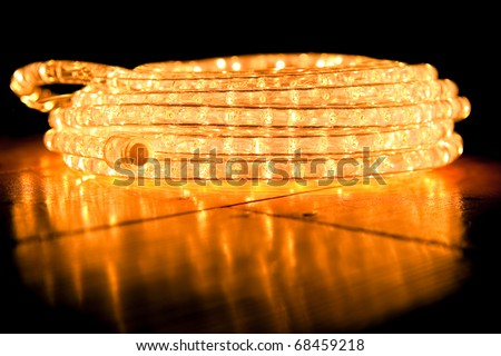 festive abstract of coiled rope lighting on a reflective hardwood floor - stock photo