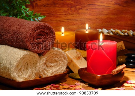 Festive aromatherapy pillar candles burning with a soft glowing flame and cotton bath towels for a soothing relaxation and pampering treatment holiday gift session in a wellness spa - stock photo