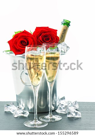 festive arrangement with sparkling wine and flowers. two glasses, bottle of champagne and red roses - stock photo