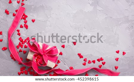 Festive background.  Gift box with red ribbon  and many little  decorative red hearts on textured grey concrete. Flat lay with copy space. - stock photo