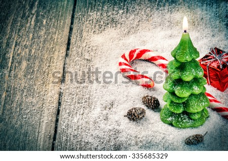 Festive background with Christmas tree candle and candy cane  - stock photo