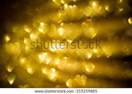 Festive background with defocused golden glitters, bokeh in a shape of a heart. - stock photo