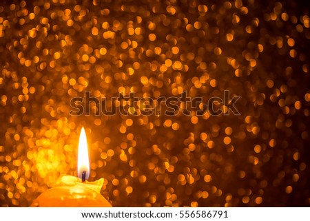 Festive background with glowing candle, sparkles and bokeh in warm colors