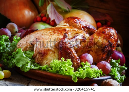 Festive baked chicken with autumn berries, fruits, nuts and vegetables in the rustic style of the old wooden background, selective focus