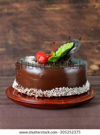 festive beautiful chocolate cake with icing and cherry - stock photo