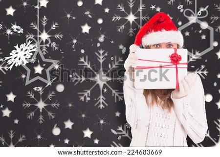 Festive blonde holding a gift against snowflake wallpaper pattern - stock photo