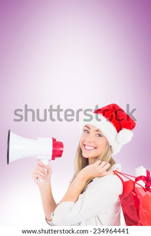 Festive blonde holding megaphone and bags on vignette background - stock photo