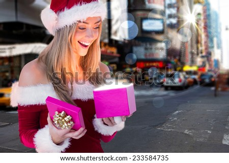 Festive blonde opening a gift against blurry new york street - stock photo