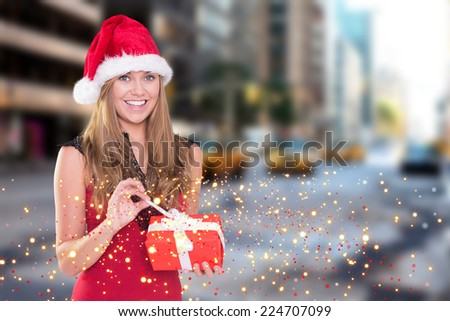 Festive blonde opening a gift against new york street - stock photo