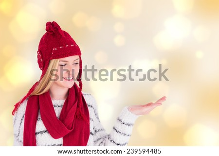 Festive blonde presenting with hand against yellow abstract light spot design - stock photo