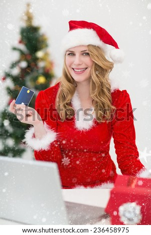Festive blonde shopping online with laptop against snow falling - stock photo