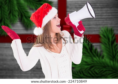 Festive blonde shouting through megaphone against festive bow over wood - stock photo