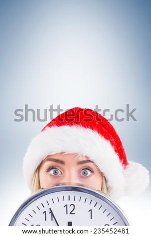 Festive blonde showing a clock on vignette background - stock photo
