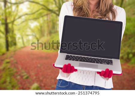 Festive blonde showing a laptop against peaceful autumn scene in forest - stock photo