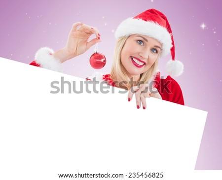 Festive blonde showing white card on vignette background - stock photo