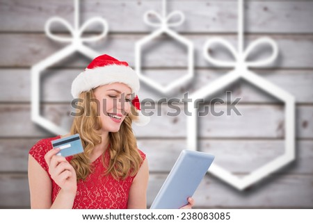 Festive blonde woman using her credit card and tablet pc against blurred christmas background - stock photo