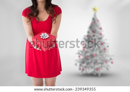 Festive brunette holding red gift against blurry christmas tree in room - stock photo
