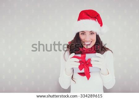 Festive brunette in santa hat holding gift against room with wooden floor - stock photo