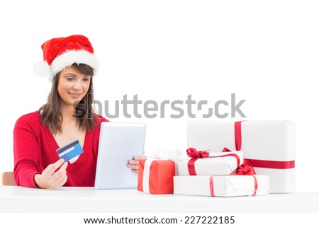 Festive brunette shopping online with tablet pc on white background - stock photo