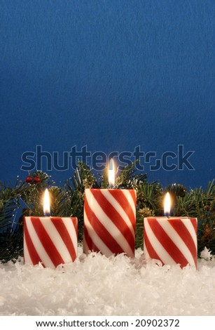 festive candy cane candles with snow, evergreen branches against a blue felt background and room for copy