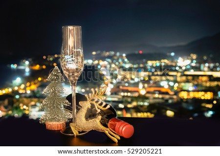 festive celebration background and texture , empty of champagne glass , bottle of wine and decoration on dark stone table blurred bokeh background,