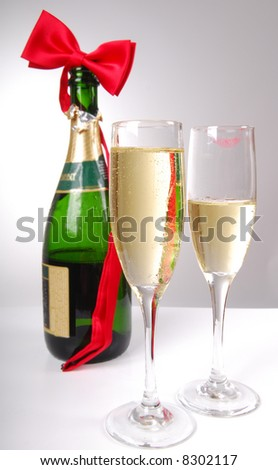 Festive champagne and bowtie with lipstick smudge on one glass