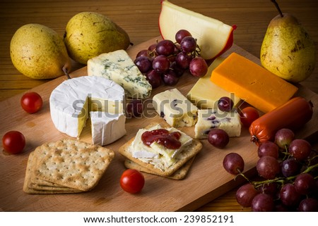 Festive cheese platter with crackers and grapes on wooden board for Christmas party. Rustic cheese selection with fruit and vegetables for new years 2016