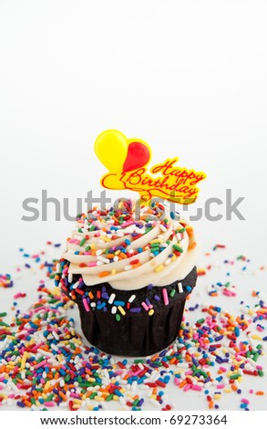 Festive Chocolate Cupcake Topped with Colorful Sprinkles and Happy Birthday Sign on White Background - stock photo