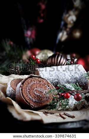 Festive chocolate Yule log in Christmas setting with generous accommodation for copy space. Concept image for your Thanksgiving or Christmas dessert menu designs. - stock photo