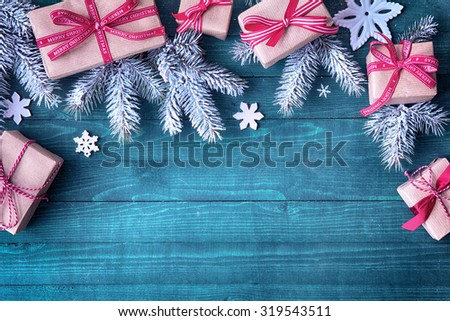 Festive Christmas border with decorative gifts tied with red bows amongst pine branches and snowflakes rustic green wood background with copyspace - stock photo