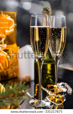 Festive Christmas champagne in two elegant flutes with gold wrapped gifts and twirled golden party streamers - stock photo