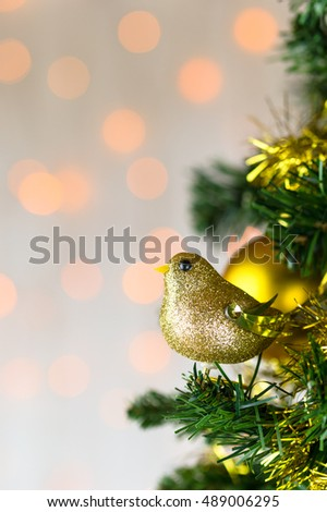 Festive Christmas close up of tree decorated with gold glitter robin, tinsel and bauble. Bokeh copy space. Vertical.