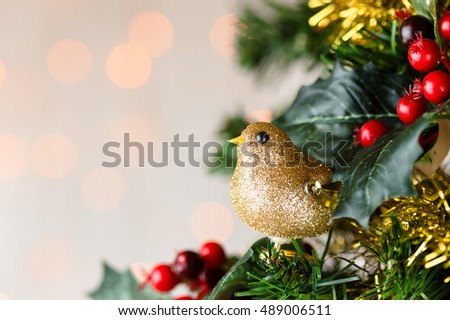 Festive Christmas close up of tree decorated with gold glitter robin, tinsel and holly berries. Bokeh copy space.
