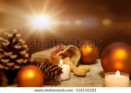 Festive christmas decoration in orange and white, lightning candles, fir cones, christmas balls and wooden background - stock photo