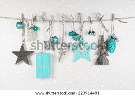 Festive christmas decoration in white an light blue on wooden background. - stock photo
