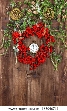 festive christmas decoration with wreath from red berries over rustic wooden background