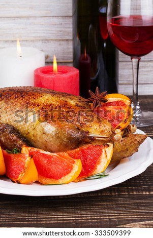Festive Christmas duck baked with grapefruits and rosemary, glass of wine and candles - stock photo