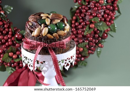 Festive Christmas food, fruit cake with glace cherries and nuts on white cake stand with holiday berry wreath in green background. Selective focus. - stock photo