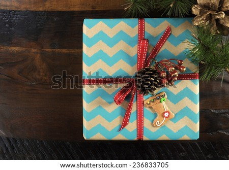 Festive Christmas gift box with chevron stripe wrapping on dark recycled wood table. - stock photo