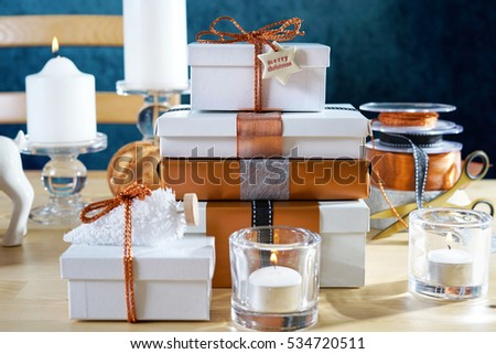 Festive Christmas gifts and gift wrapping in copper and white theme, with candles and ornaments on a natural wood table against a blue background.