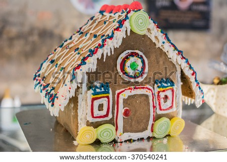 Festive Christmas Gingerbread House decorated with candy canes, marshmallow cones, chocolates and candy in a rustic dark wood setting.  - stock photo