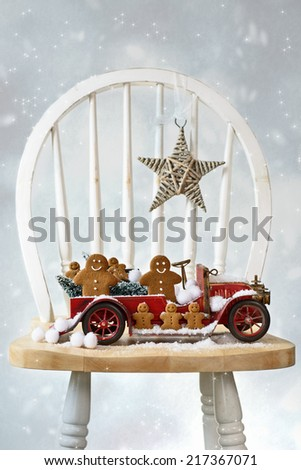 Festive Christmas gingerbread men sitting in vintage red truck with snow - stock photo