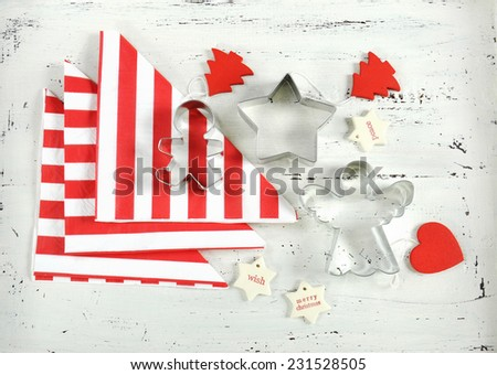 Festive Christmas Holiday background with red and white theme cookie cutters and stripe napkins on vintage shabby chic white wood background.