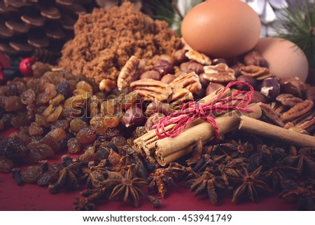 Festive Christmas spices and ingredients on dark red wood background for holiday baking and cooking concept, with applied retro style filters.  - stock photo