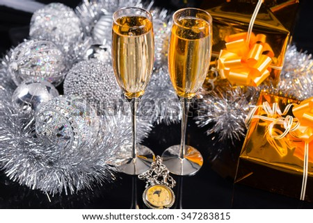 Festive Christmas Still Life - Pair of Champagne Glasses in Glittering Still Life with Gold Wrapped Presents, Silver Tinsel Garland and Decorative Ornaments