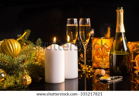 Festive Christmas still life with champagne in a bottle and flutes, burning white candles and golden gifts and baubles over a dark background - stock photo