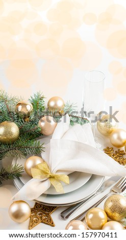 Festive Christmas table setting, table decorations in gold tones, with fir branches, baubles, decorations. - stock photo
